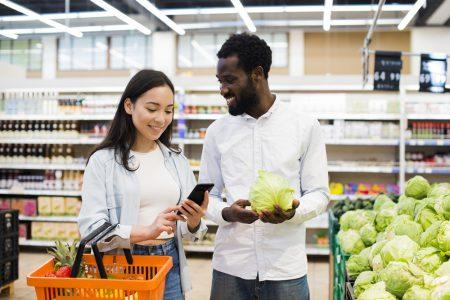 casal feliz escolhendo verduras no supermercado